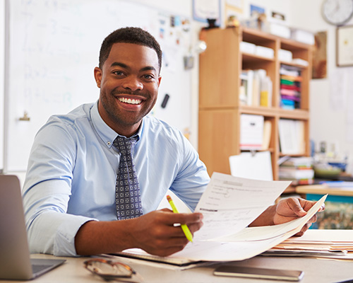 A smiling teacher at his desk in a classroom.