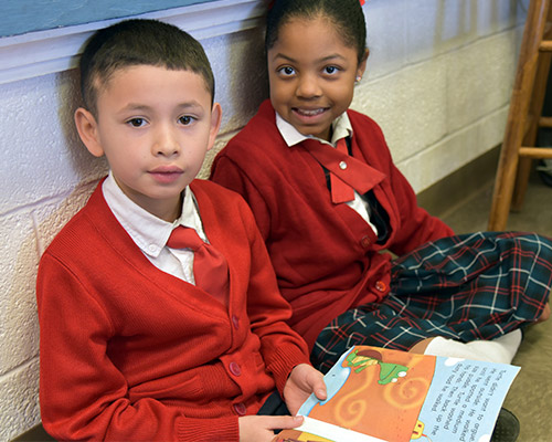 Two school children read a book together.