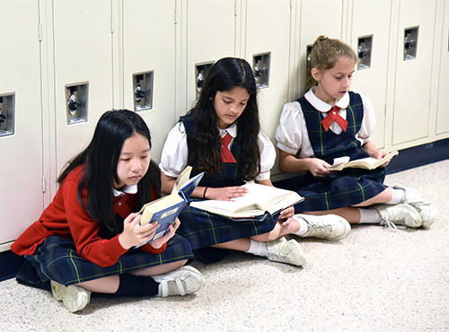 Three students sit quietly on the floor and read.
